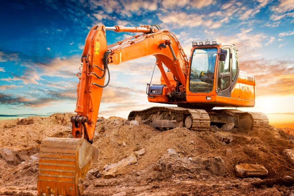 Excavator at a construction site against the setting sun. High quality image.